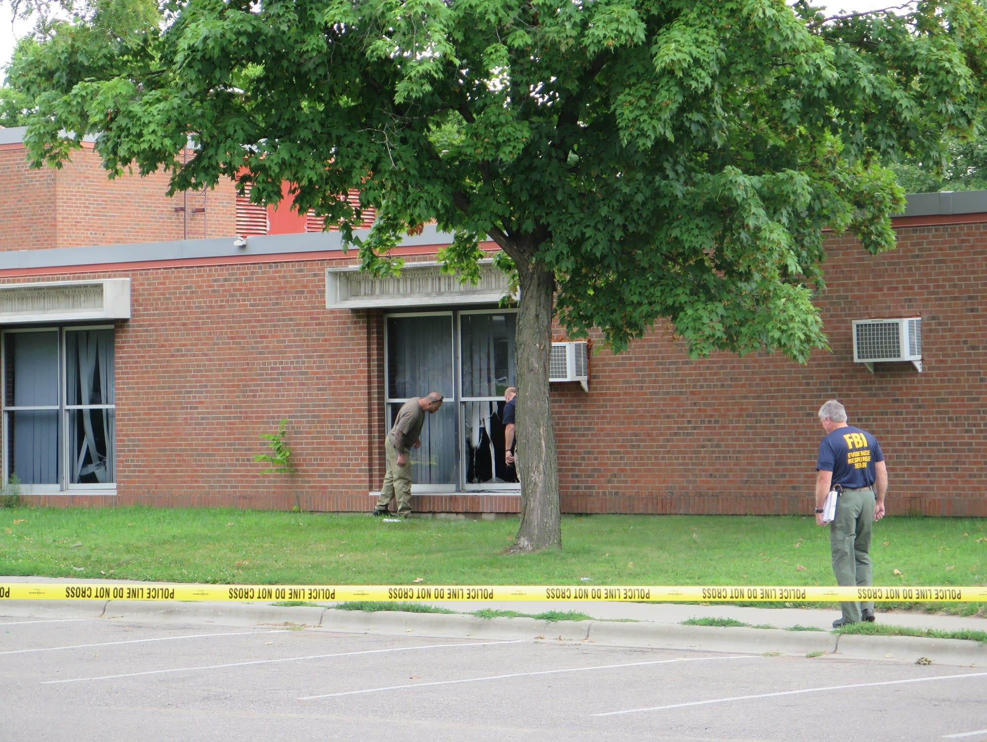 FBI agents and others inspect the site on an explosion.