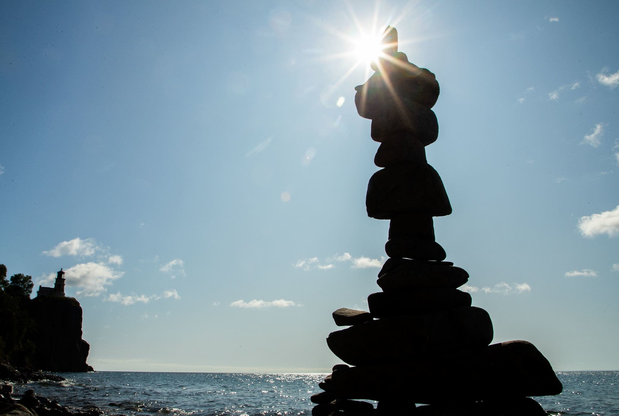 A tall stack of rocks is silhouetted against a blue sky.