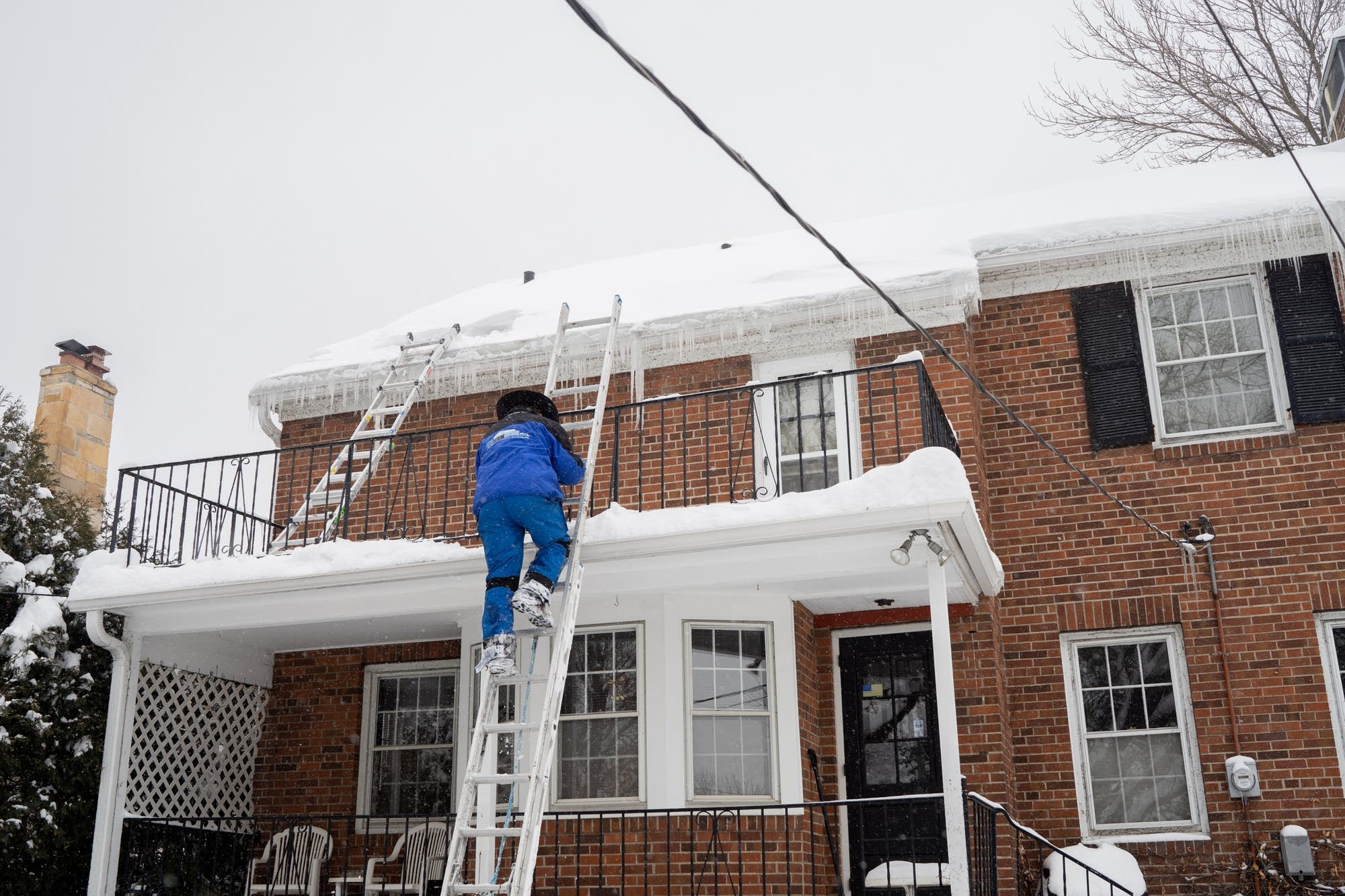 An Ice Dam Guys technician climbs to the roof of a St. Paul home.