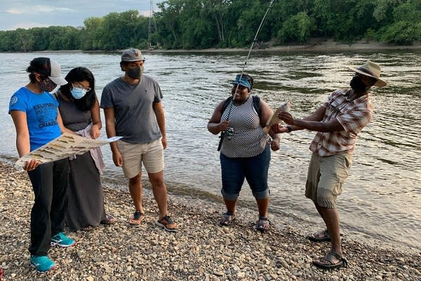 A group of people enjoy fishing by a river.