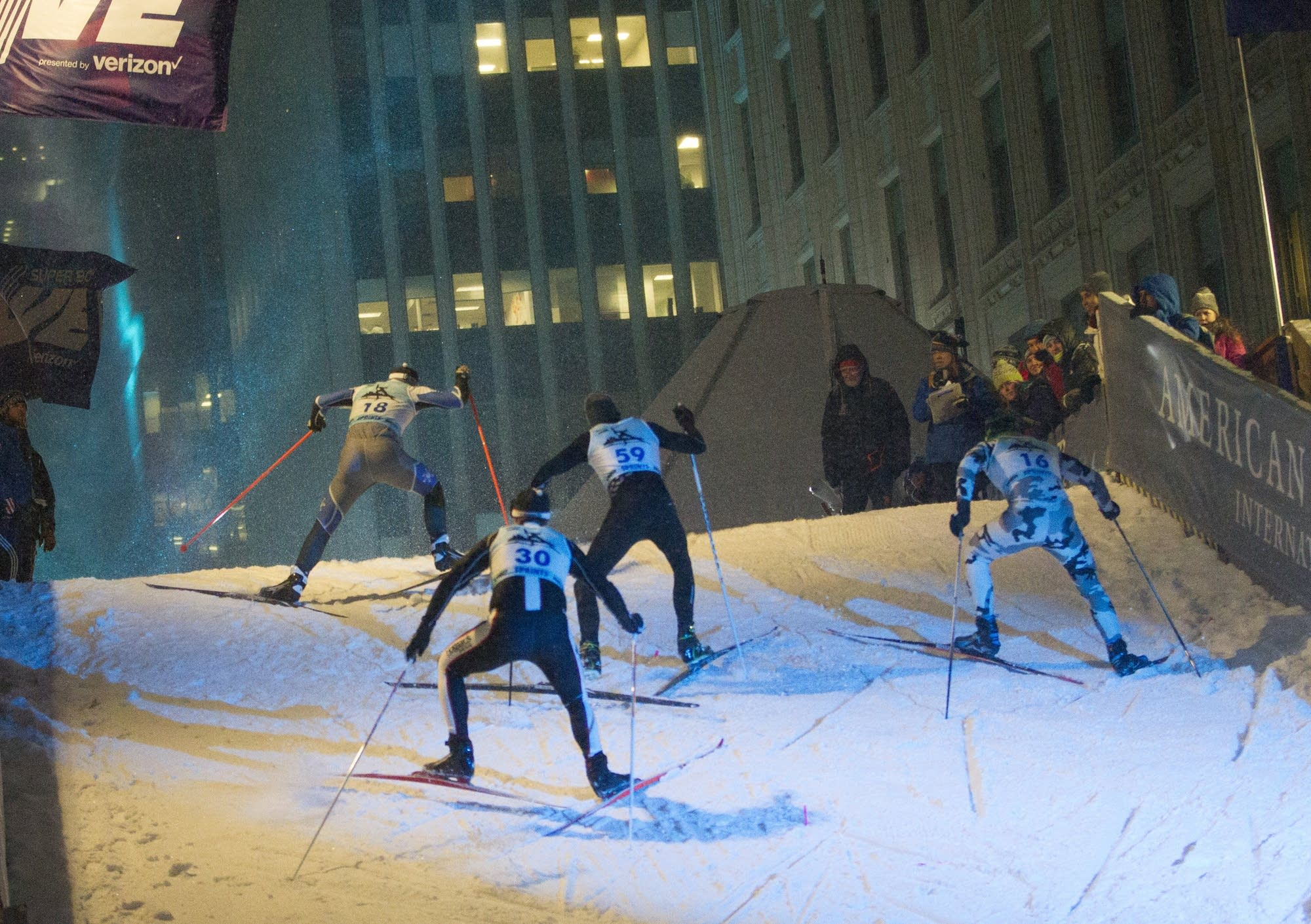 With downtown in the background, elite adult skiers climb the hill.
