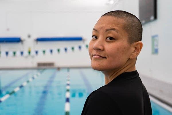 Jae Hyun Shim poses for a portrait near a swimming pool.
