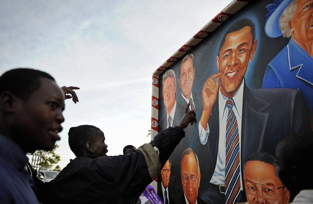 Villagers of Kogelo point at a poster of Obama