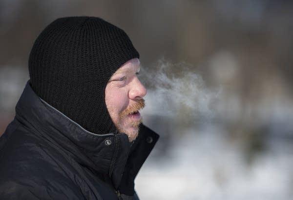 A man wearing a black balaclava and heavy coat.