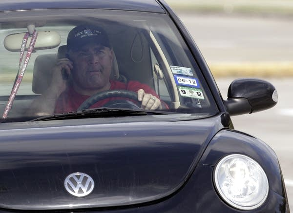 A driver uses a cellphone on the road.
