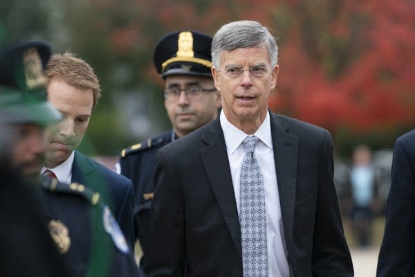 A man in a suit is escorted by security
