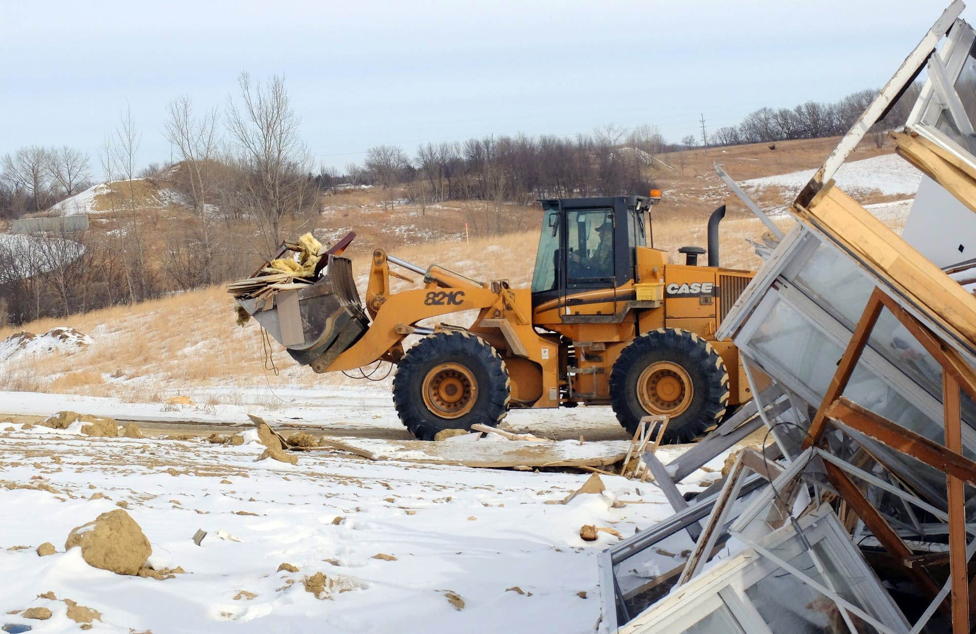 A worker moves debris with a loader at the Fergus Falls landfill.