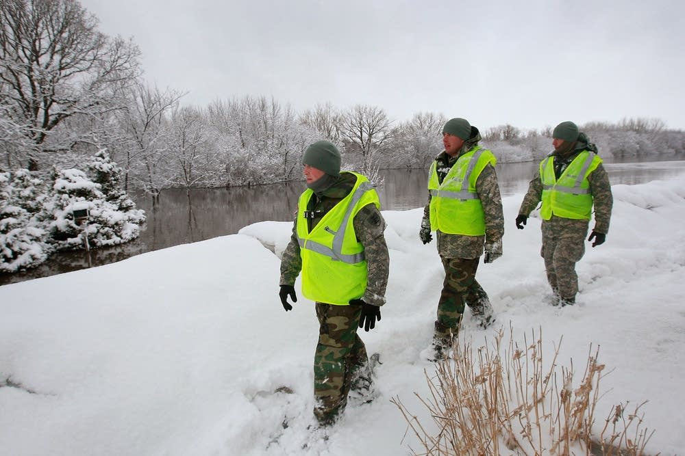 Guard members inspect a levee
