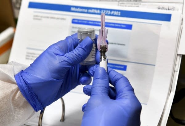 Gloved hands hold a syringe and vaccine vial.