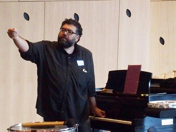 Ahmed Anzaldúa warms up the choir at a rehearsal.