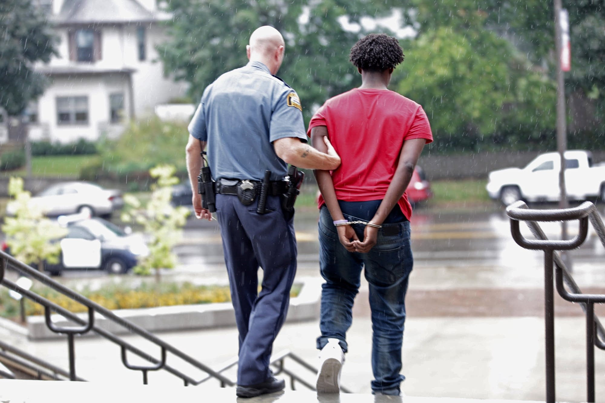 A St. Paul Central High student is escorted out of the school in handcuffs.