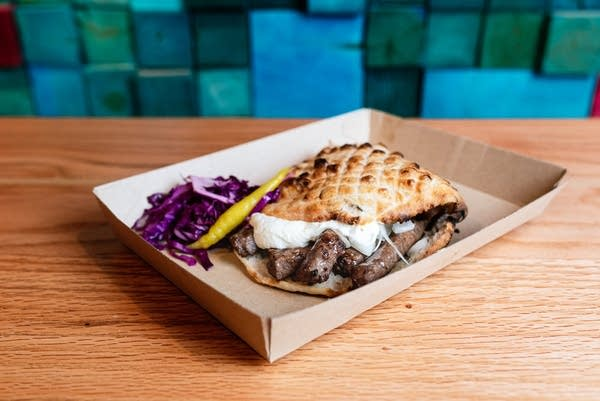 Balkan Treat Box's signature cevapi, grilled beef sausages in somun, kajmak and onion
