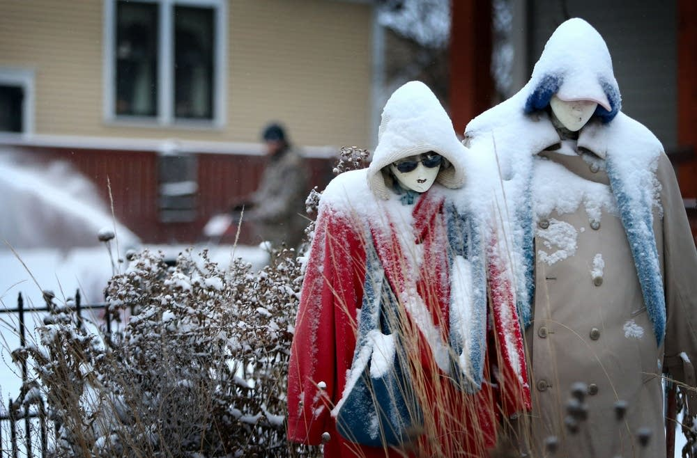 Scarecrows in a garden wear snow shrouds.