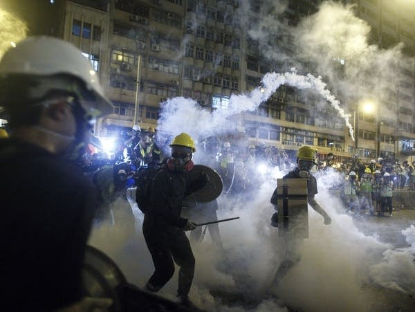 Protesters react to tear gas during a confrontation with riot police