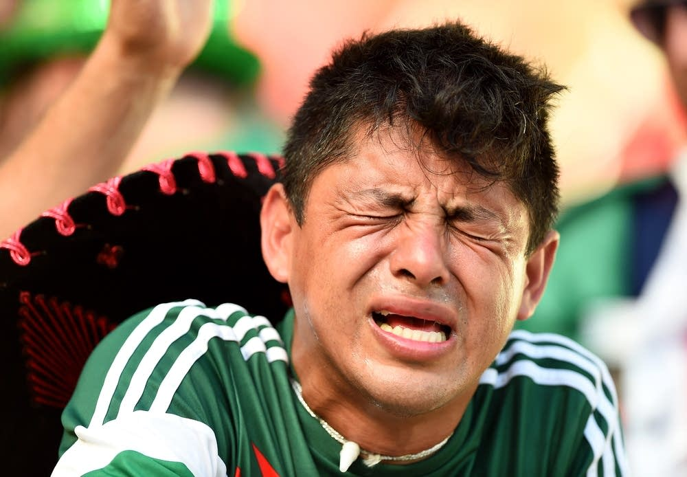 A dejected Mexico fan reacts