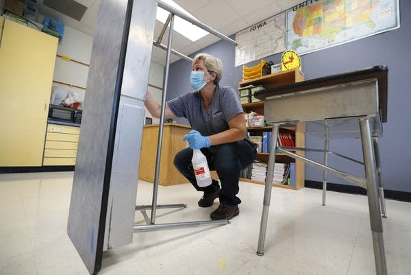 A school custodian cleans a desk in a classroom.