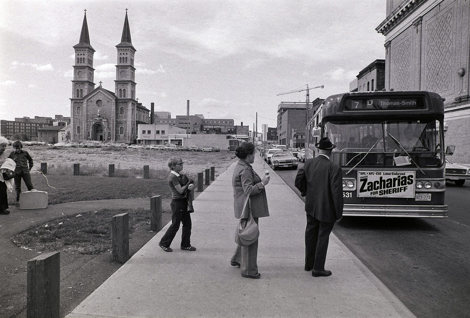 Bus riders wait to board an MTC bus on St. Peter St., behind the Palace.