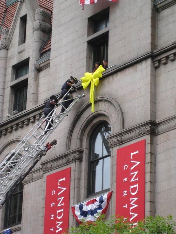 Firefighters hang a ribbon on the Landmark Center
