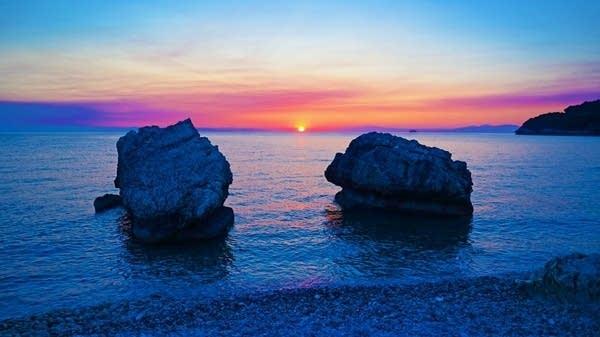 large rocks along a seashore at sunset