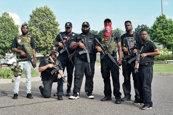A group of men with guns stand for a photo.