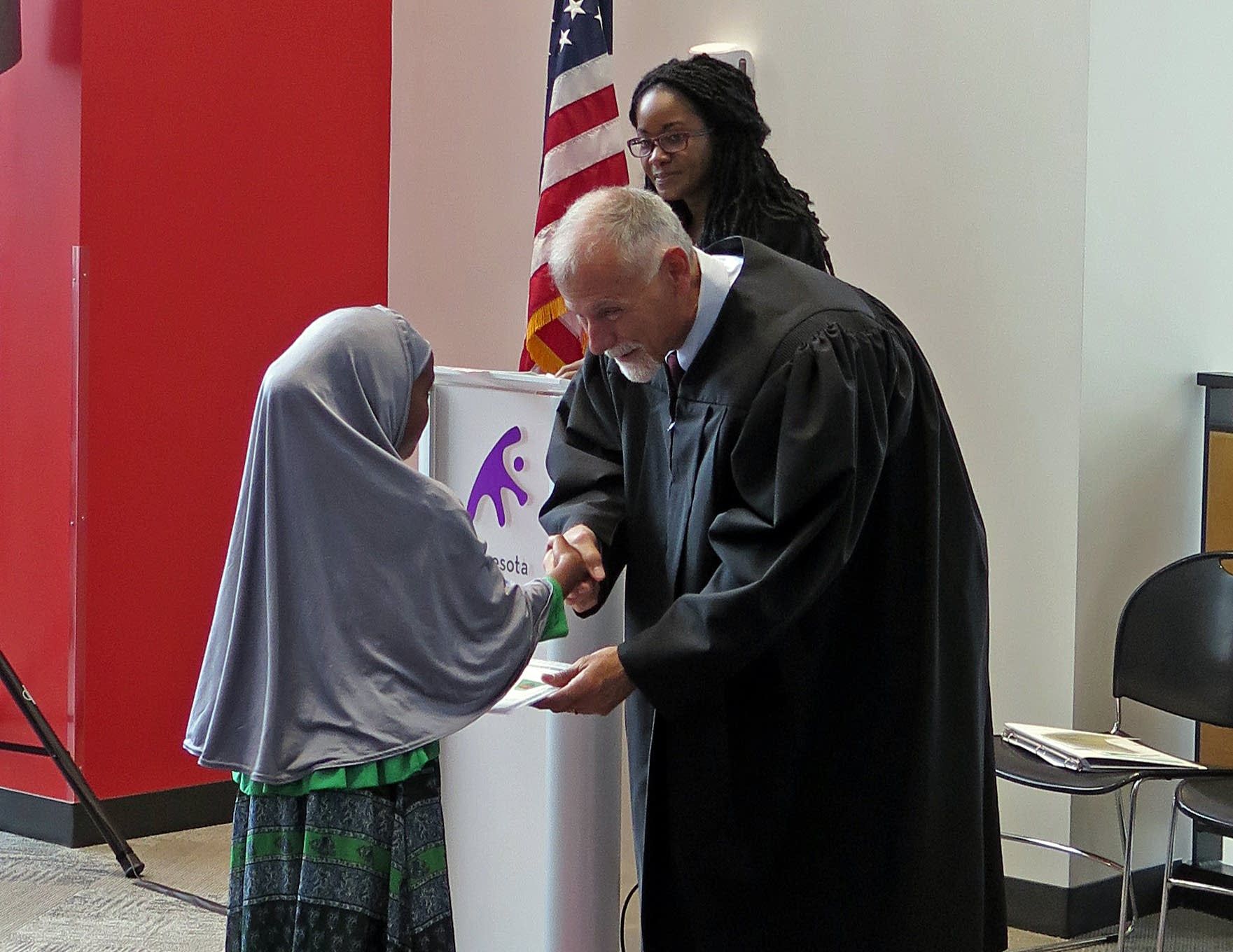 Judge David T. Schultz handed certificates to new, young citizens.