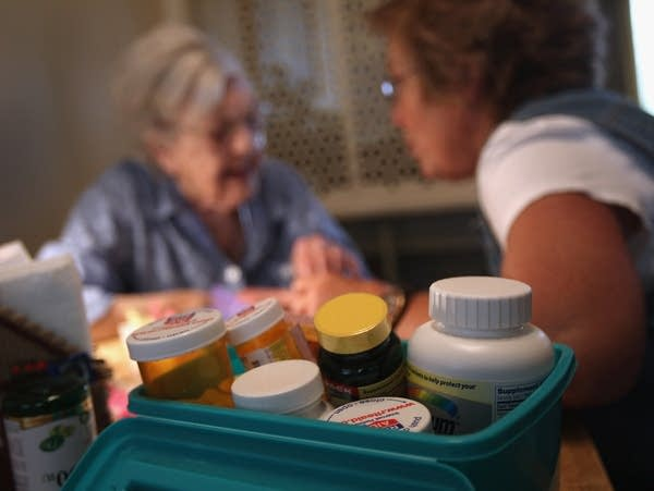 Pill bottles are shown, with a health care provider talking to a client.