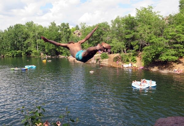 A visitor jumps off a rock ledge at Quarry Park and Nature Preserve.