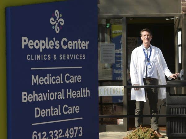 A man in a white coat stands outside the door of a clinic.