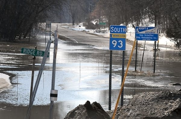 Water flows across State Highway 93 south of Henderson, Minn.