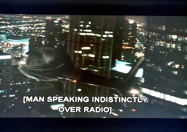 "TV with caption that reads ""Man speaking indistinctly over radio"""