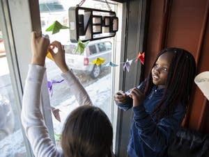 Lydia Kumbo, 10, and Nixzmarely Chavelas, 10, hang up origami butterflies.