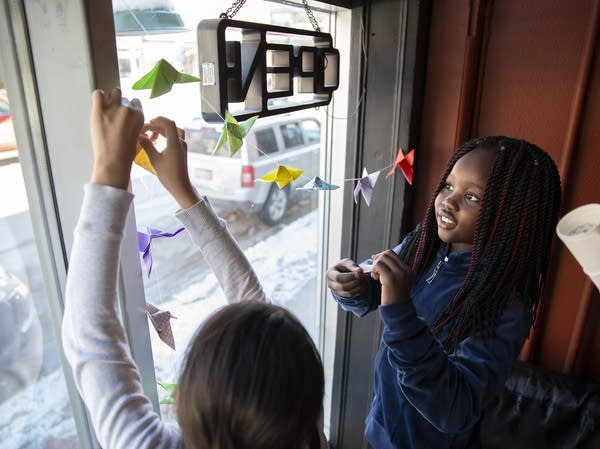 Lydia Kumbo, 10, and Nixzmarely Chavelas, 10, hang up origami butterflies.