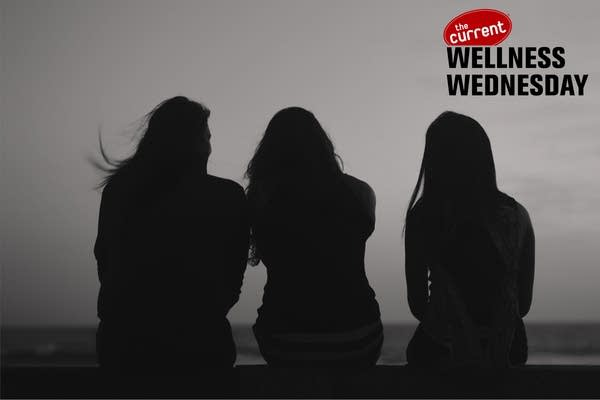 Silhouette of three women seen from behind.