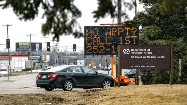"""A car drives near a road sign that reads """"No appt? Call 1st"""""""