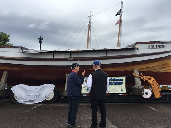 Two people stand in front of a replica of a Viking ship.
