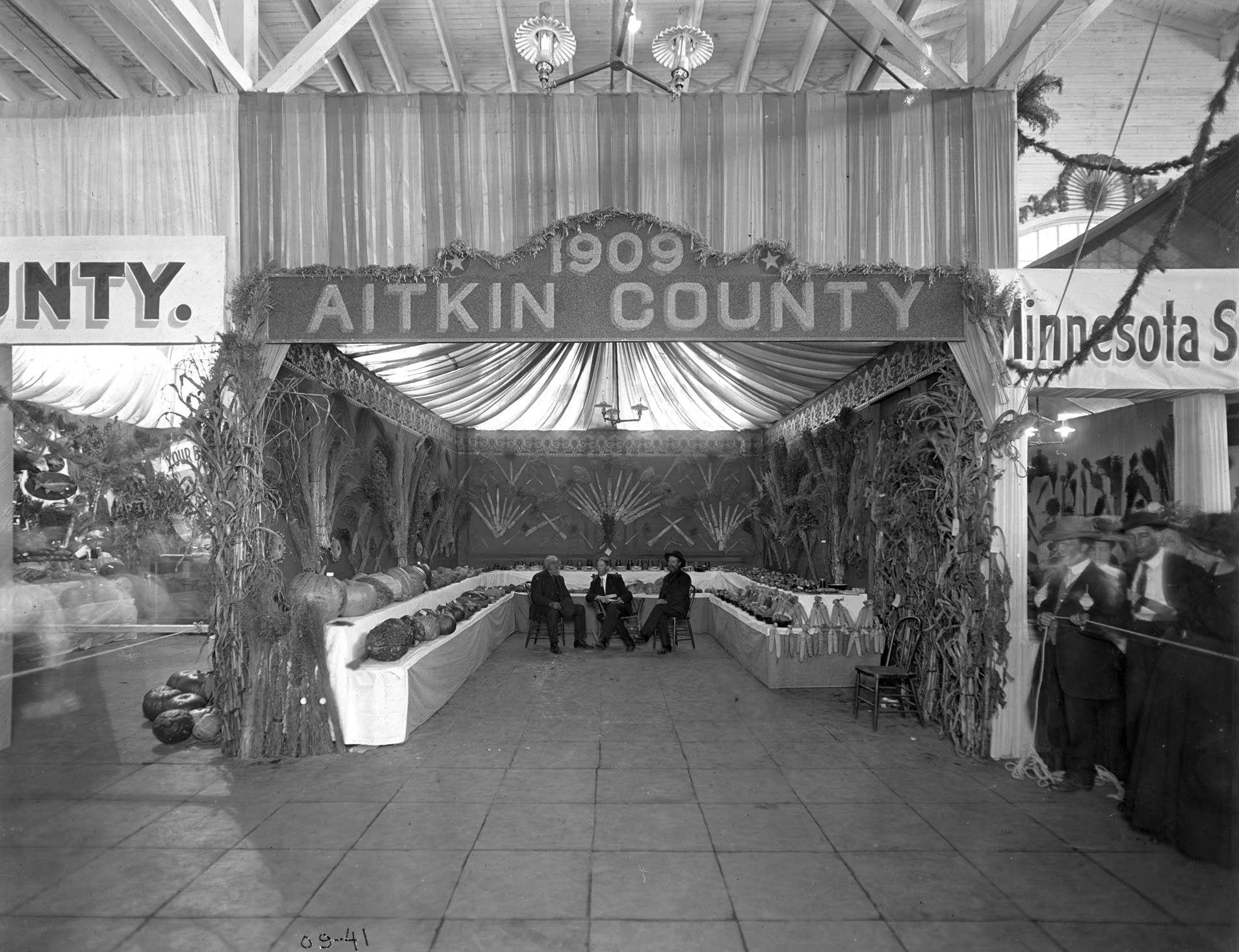 The Aitkin County booth featured corn, large gourds, potatoes in 1909.