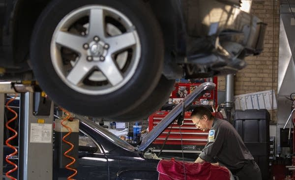 A person works under the hood of a car.