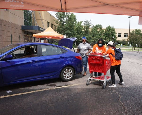 People unload items from a shopping cart.