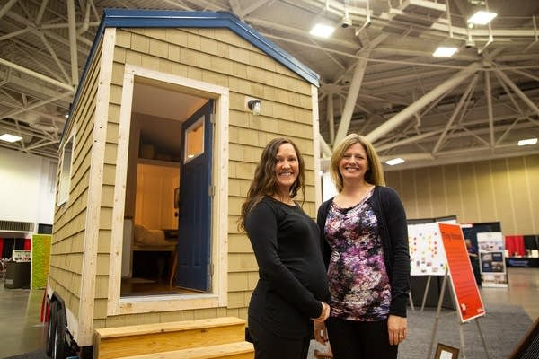 Two women stand in front of a tiny home inside of a building.