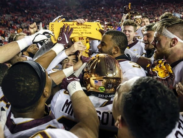 Minnesota players celebrate with the Paul Bunyan Axe