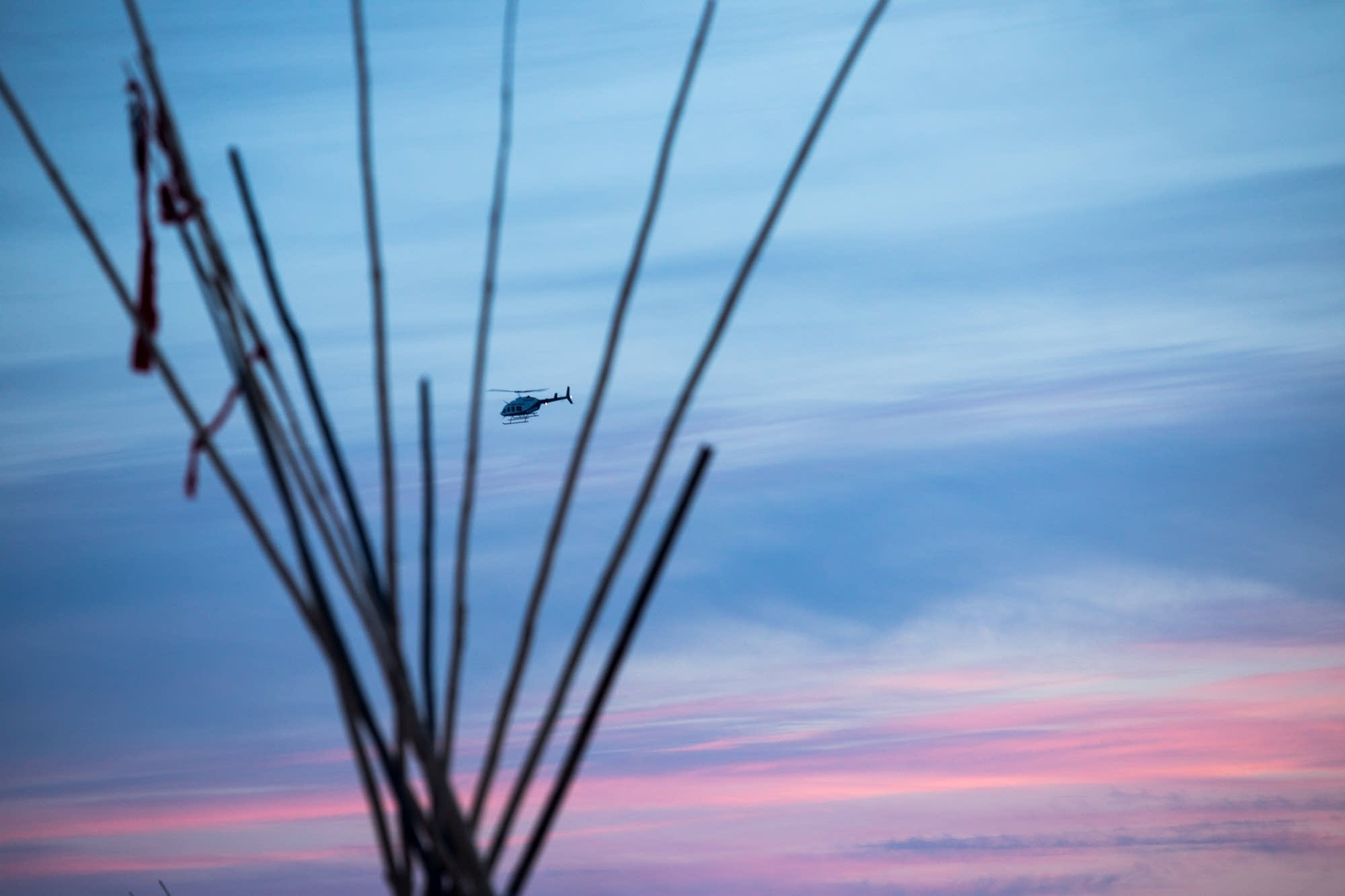 A surveillance helicopter flies over camp.