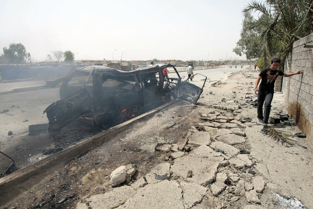 An Iraqi boy walks past a burning vehicle