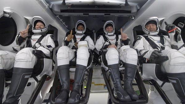 Astronauts inside a space crew capsule