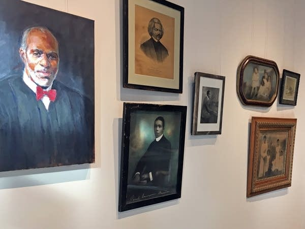 A portrait of Alan Page hangs beside portraits of other African Americans.