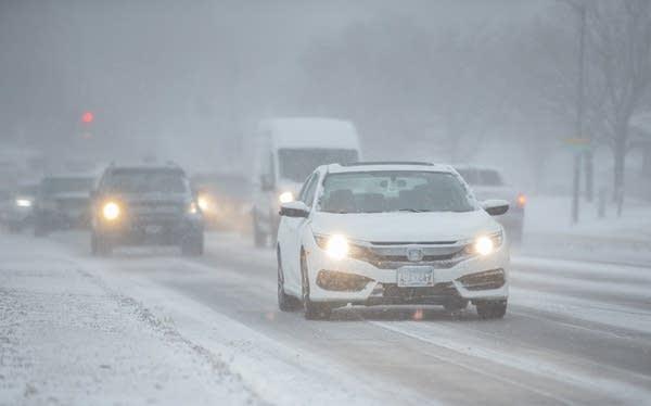 Cars drive through the snow.