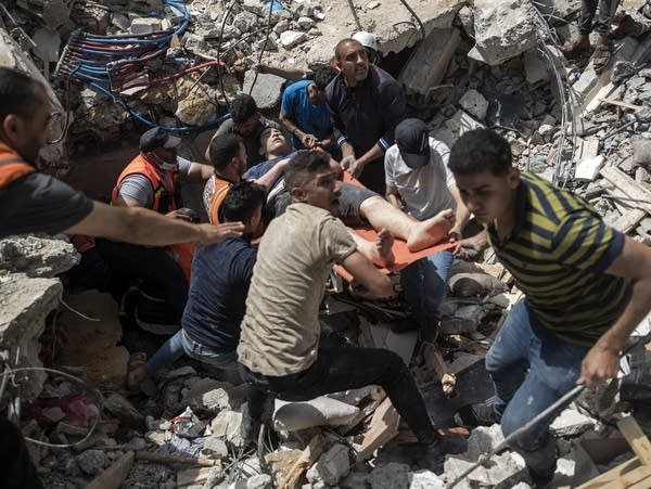 People rescue a person from the rubble of a destroyed building