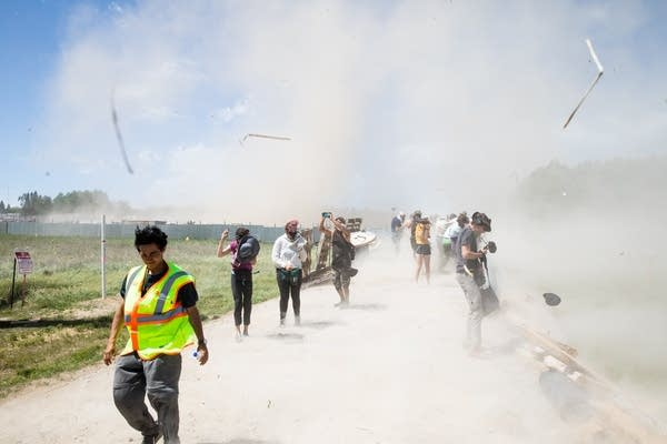 People stand in a cloud a dust from a helicopter.