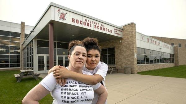 A student hugs her mother over her shoulder.