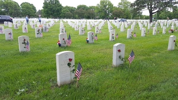 Flags and flowers sit in front of headstones
