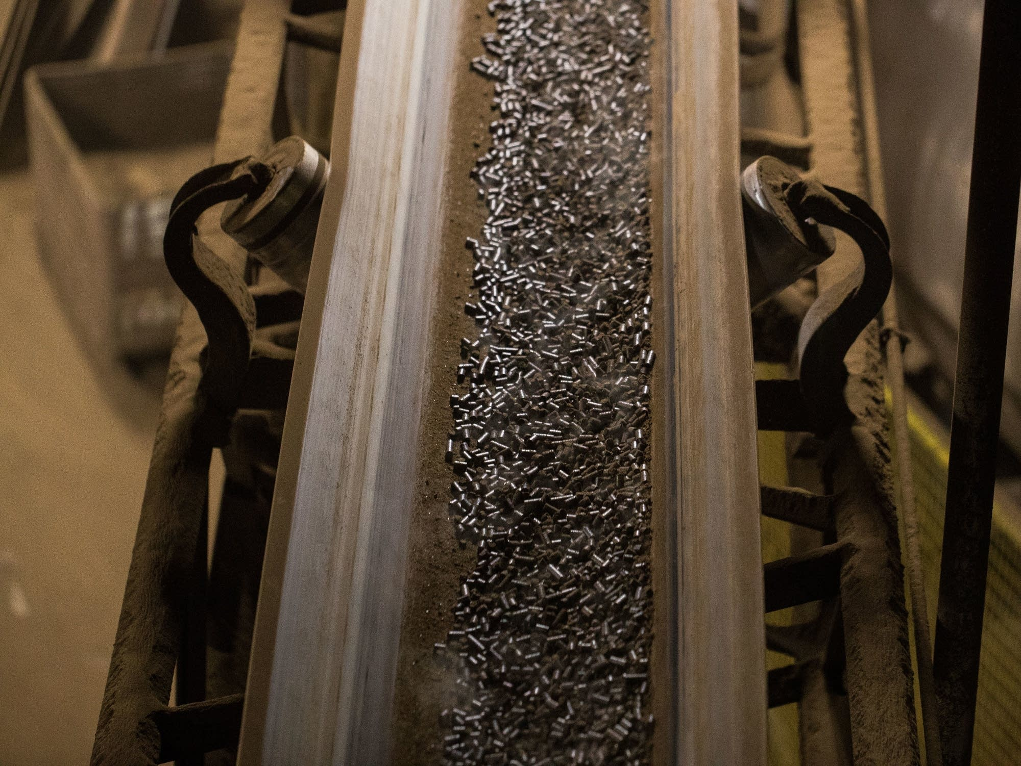 Steaming peat that has been pelletized rides along a conveyor belt